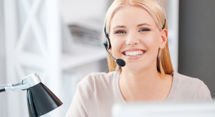 Always ready to help you. Happy young woman in headset looking at camera and smiling while sitting at her working place